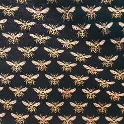 Tissus Jacquard HONEY brodé d'abeilles dorées sur un fond noir.