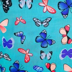 Tissu Viscose imprimée de papillons multicolores sur un fond bleu turquoise.