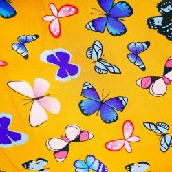 Tissu Viscose imprimée de papillons multicolores sur un fond jaune.
